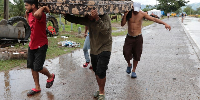 Neighbors help each other as they evacuate the area before Hurricane Iota makes landfall in San Manuel Cortes, Honduras, Monday, November 16, 2020.