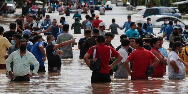 Residents wade through a flooded road in the aftermath of Hurricane Eta in Planeta, Honduras, 11 월. 5, 2020.