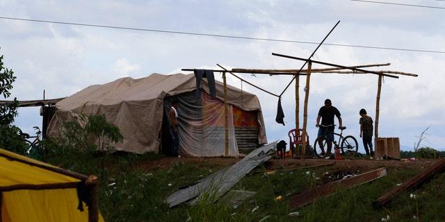 People living under precarious conditions make preparations before Hurricane Iota makes landfall in San Manuel Cortes, Honduras, Monday, Nov. 16, 2020.