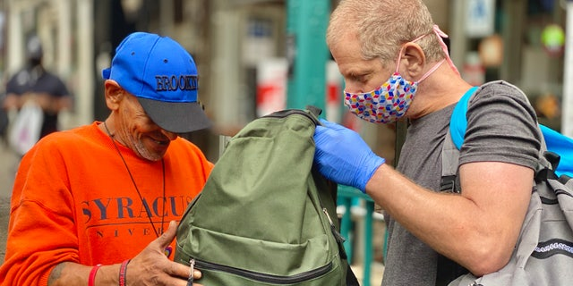 Jeffrey Newman (right) is giving someone a backpack filled with necessities. (Courtesy of Backpacks for the Street)