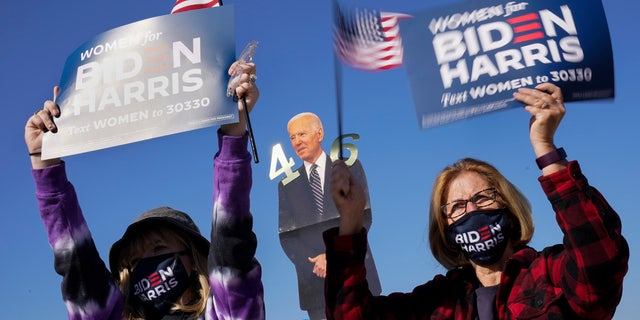 Supporters listen as Democratic presidential candidate former Vice President Joe Biden speaks at a rally at the Iowa State Fairgrounds in Des Moines, Iowa, Friday, Oct. 30, 2020.