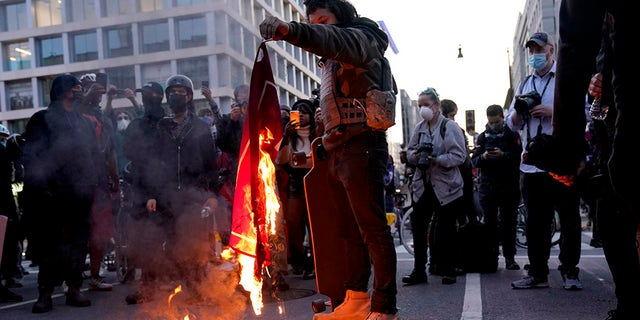 A counter-protester burns a Trump 2020 flag after supporters of President Donald Trump held pro-Trump marches on Saturday in Washington. (AP Photo/Jacquelyn Martin)