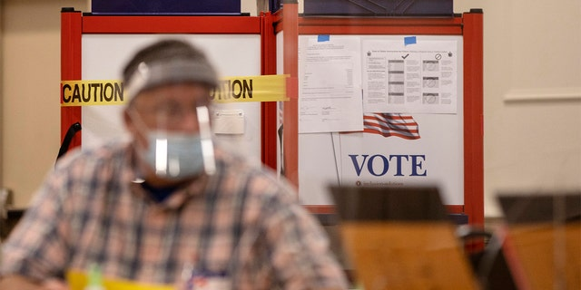 A voting booth with sides blocked off with caution tape to ensure social distancing at the Italian Heritage Center in Portland, Maine. (Staff photo by Brianna Soukup/Portland Press Herald via Getty Images)