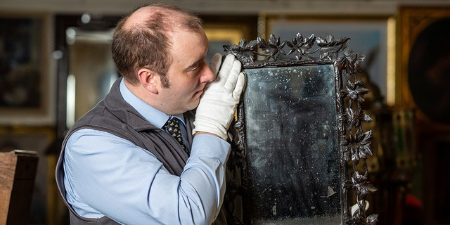 A family is expected to earn thousands from the sale of an antique mirror passed between generations.