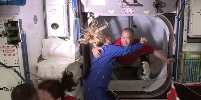 In this frame grab from NASA TV, astronaut Soichi Noguchi, background right, is greeted by astronaut Kate Rubins, as he enters the International Space Station from the vestibule between the SpaceX Dragon capsule and the ISS, early Tuesday, Nov. 17, 2020.