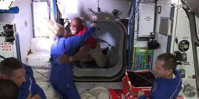 In this frame grab from NASA TV, astronaut Victor Glover, center, is greeted by astronaut Kate Rubins as he enters the International Space Station from the vestibule between the SpaceX Dragon capsule and the ISS, early Tuesday, Nov. 17, 2020. At right is Expedition 64 commander Sergey Ryzhikov. (NASA TV via AP)