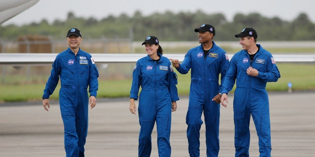 Astronaut Soichi Noguchi, of Japan, 왼쪽에서, NASA Astronauts Shannon Walker, Victor Glover and Michael Hopkins walk after arriving at Kennedy Space Center, 일요일, 11 월. 8, 2020, in Cape Canaveral, Fla.