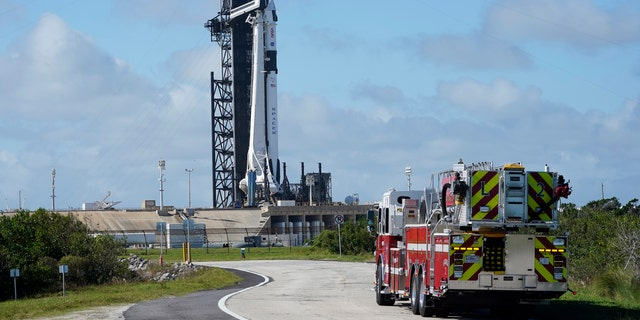 NASA firefighters drive on the road outside the fence near a SpaceX Falcon 9 rocket, with the company's Crew Dragon capsule attached, sits on the launch pad at Launch Complex 39A Friday, 11 월. 13, 2020, at the Kennedy Space Center in Cape Canaveral, Fla.