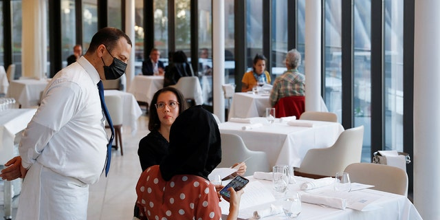 A waiter tends to patrons in the Mediterranean seafood restaurant Estiatorio Milos at the Hudson Yards in Manhattan, New York, Sept. 30, 2020. (REUTERS/Andrew Kelly)