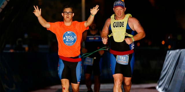 Chris Nikic and his guide Dan Grieb cross the finish line of IRONMAN Florida on Nov. 7 in Panama City Beach, Florida. Chris Nikic became the first Ironman finisher with Down syndrome. (Photo by Michael Reaves/Getty Images for IRONMAN)