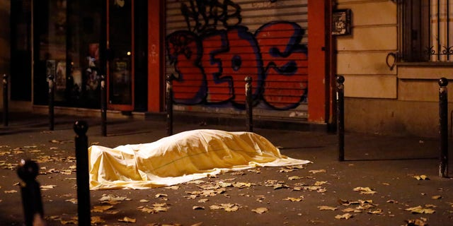 FILE - In this Nov. 13, 2015 file photo, a victim of an attack in Paris lays dead outside the Bataclan theater in Paris. In the aftermath of the horrifying attacks in Paris on Nov. 13, 2015, people were so jittery that some loud, unremarkable noises were enough to send some people scurrying for help. Some experts say it will take months for Europeans to adapt to life after the paris attacks. (AP Photo/Jerome Delay, File)