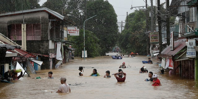 Due to Typhoon Vamco on Thursday, November 12, 2020, the Marikina, Philippines, floods continue to rise, and residents are negotiating a flooded road.