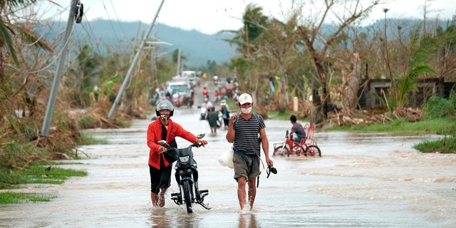 On Thursday, November 12, 2020, due to Typhoon Vamco, residents walked past overturned electric poles along a flooded road in Albay Province in the central Philippines.