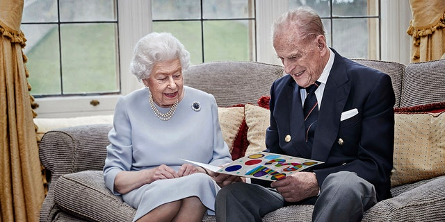 In this image released on Thursday, Nov. 19, 2020, Britain's Queen Elizabeth II and Prince Philip, Duke of Edinburgh look at a homemade wedding anniversary card, given to them by their great-grandchildren.