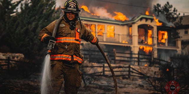 A firefighter helps to battle a blaze that engulfed a home in a Reno neighborhood on Tuesday.