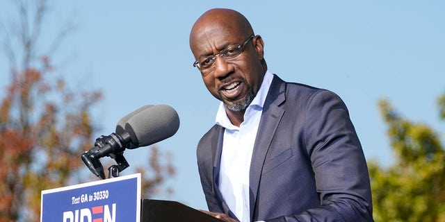 Raphael Warnock, a Democratic candidate for the U.S. Senate, speaks to Biden supporters as they wait for former President Barack Obama to arrive and speak at a rally as he campaigns for Democratic presidential candidate former Vice President Joe Biden, Monday, Nov. 2, 2020, at Turner Field in Atlanta. (AP Photo/Brynn Anderson)