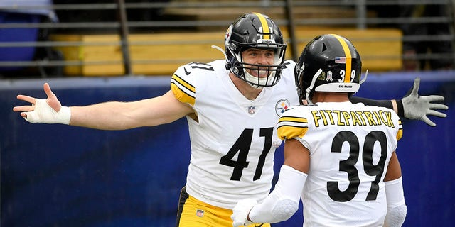 Pittsburgh Steelers linebacker Robert Spillane, left, celebrates with free safety Minkah Fitzpatrick after scoring on an interception of a pass from Baltimore Ravens quarterback Lamar Jackson, not visible, during the first half of an NFL football game, Sunday, Nov. 1, 2020, in Baltimore. (AP Photo/Nick Wass)