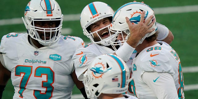 Miami Dolphins quarterback Ryan Fitzpatrick, sentrum, celebrates a touchdown with Adam Shaheen, reg, during the second half of an NFL football game against the New York Jets, Sondag, Nov.. 29, 2020, in East Rutherford, N.J. (AP Photo/Corey Sipkin)