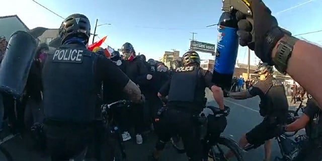 Seattle police officers move back a crowd during a Sept. 7 protest.