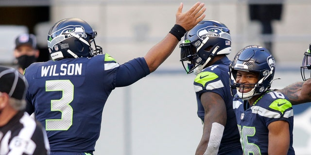 Il quarterback dei Seattle Seahawks Russell Wilson (3) celebrates with wide receiver DK Metcalf, centro, after Wilson passed to Metcalf for a touchdown against the San Francisco 49ers during the first half of an NFL football game, Domenica, Nov. 1, 2020, a Seattle. (AP Photo / Scott Eklund)