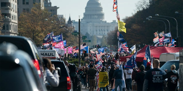 A motorcade carrying President Donald Trump drives by a group of supporters participating in a rally near the White House, Nov. 14, in Washington. (AP Photo/Evan Vucci)