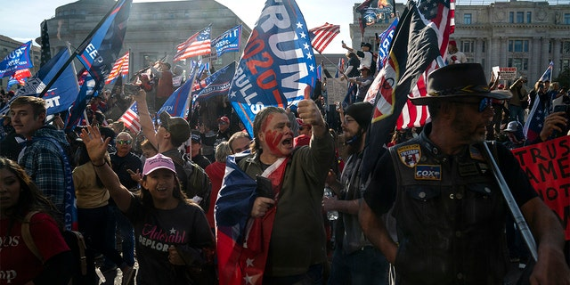 Supporters of President Donald Trump cheer as his motorcade drives past a rally of supporters near the White House, Saturday, Nov. 14, 2020, in Washington. (AP Photo/Evan Vucci)