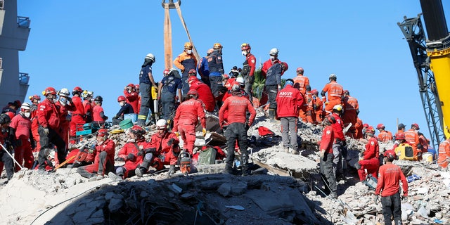 Members of rescue services search in the debris of a collapsed building for survivors in Izmir, 터키, early Sunday, 11 월. 1, 2020.