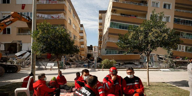 Members of rescue services take a break during search operations in the debris of a collapsed building for survivors in Izmir, Turkey, Sunday, Nov. 1, 2020.