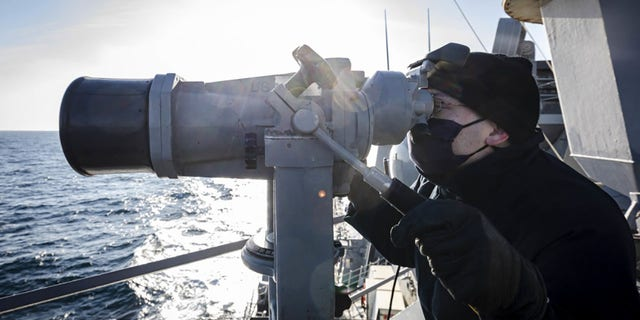 Ensign James Bateman, from Huntsville, Ala., scans the horizon utilizing the 'big eyes' while standing watch on the on the bridge wing of the guided-missile destroyer USS John S. McCain on Tuesday.