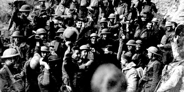 American troops cheer after hearing the news that the Armistice has been signed, ending World War I in November 1918. They are located on the front northeast of St. Mihiel, France. Similar celebrations took place all along the line where the Americans were engaged in an offensive. (AP photo)