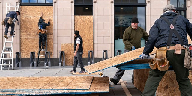 Ahead of the presidential election, workers with Baguer Construction LLC board up a Walgreens on U Street NW in Washington, D.C. on Friday. The site manager said they had been hired to put protective coverings on several Walgreens throughout the city. (AP Photo/Jacquelyn Martin)