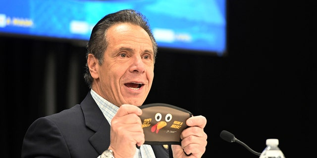 In this provided by the State of New York, New York Gov. Andrew Cuomo holds up a new Thanksgiving-themed face mask during his daily coronavirus briefing at the Wyandanch-Wheatley Heights Ambulance Corp. Headquarters in Wyandanch, N.Y. (Kevin P. Coughlin/State of New York via AP)