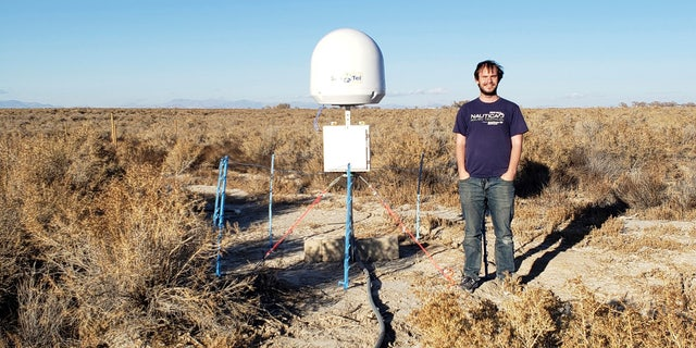 This undated photo provided by Caltech shows radio astronomer Christopher Bochenek with a STARE2 station he developed near the town of Delta, Utah. On Wednesday, Nov. 4, 2020, astronomers say they used this system and a Canadian observatory to trace an April 2020 fast cosmic radio burst to our own galaxy.
