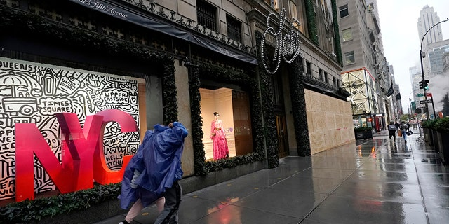 Pedestrians walk past the partially-boarded-up windows at Saks Fifth Avenue's flagship Fifth Avenue store, Sunday, Nov. 1, 2020, in New York. (AP Photo/Kathy Willens)