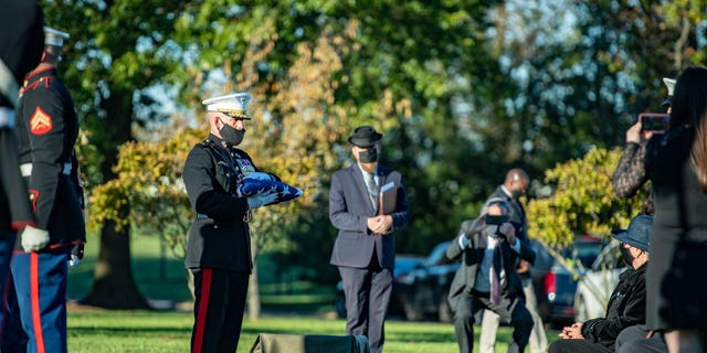 Georgie Carter-Krell, seated at right, is presented with American flag at her son Pfc. Bruce Carter's burial at Arlington National Cemetery