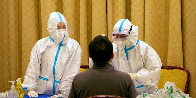 Protective suit workers are administering a COVID-19 test in Wenchang in southern China's Hainan province on Sunday.  (AP Photo / Mark Schiefelbein)