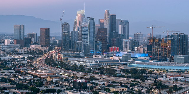 Aerial view of crowded cityscape with modern skyline and traffic, and the Los Angeles Convention Center located just beyond the freeway in Los Angeles, California, USA.