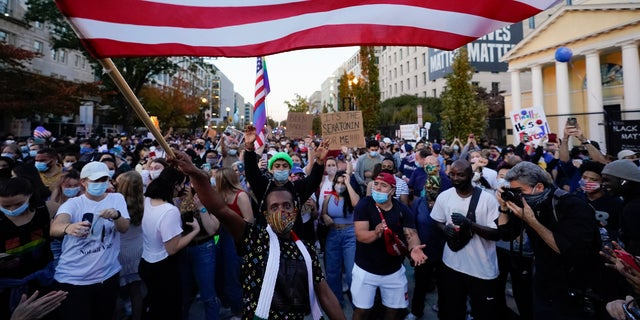 People gather in Black Lives Matter Plaza on Nov. 7, 2020, to celebrate President-elect Joe Biden's win over President Donald Trump to become the 46th president of the United States. (AP Photo/Alex Brandon, File)