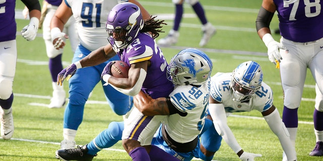 Minnesota Vikings running back Dalvin Cook (33) is tackled by Detroit Lions linebacker Jamie Collins Sr. (58) durante la prima metà di una partita di football della NFL, Domenica, Nov. 8, 2020, in Minneapolis. (AP Photo/Bruce Kluckhohn)
