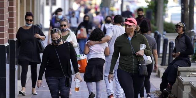 <br>In this Nov. 6, file photo, people walk in downtown Evanston, Ill. With the coronavirus coming back with a vengeance across the country and the U.S. facing a long, dark winter, governors and other elected officials are showing little appetite for reimposing the kind of lockdowns and large-scale business closings seen last spring. (AP Photo/Nam Y. Huh, File)