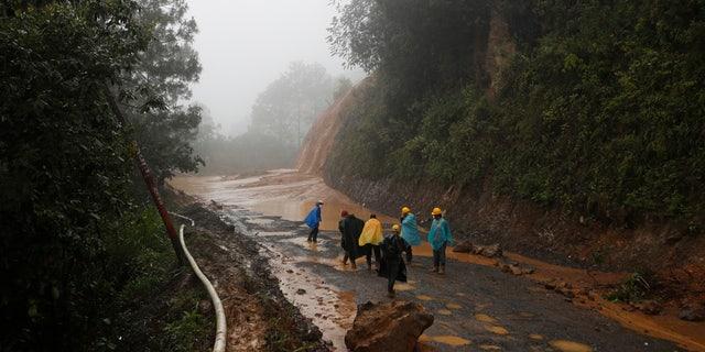 Workers walk around a road blocked by a landslide in San Cristobal Verapaz, Saturday, November 7, 2020, after hurricane Eta.