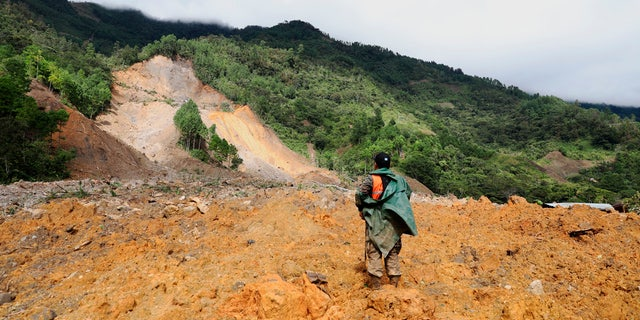 A member of the search and rescue team is looking for survivors after the devastation caused by a massive landslide caused by rain in the village of Queja, in Guatemala, Saturday, November 7, 2020, after the storm tropical Eta.