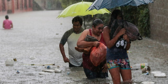 Residents wade through a flooded road carrying some belongings in Progreso Yoro, Honduras, Wednesday, Nov. 4, 2020.