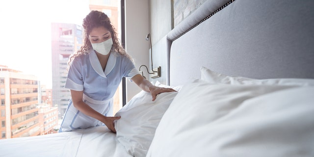Latin American maid working at a hotel and doing the bed wearing a facemask - COVID-19 pandemic lifestyle concepts