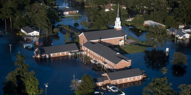 In this Monday, Sept. 17, 2018 file photo, floodwaters surround a church and other buildings in Conway, S.C., after Hurricane Florence struck the Carolinas.