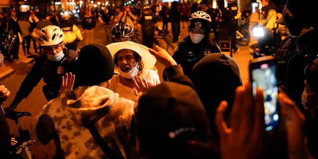 A supporter of President Trump, third from left in white hat, argues with counter-protestors after pro-Trump marches were held Saturday, Nov. 14, 2020, in Washington. (AP Photo/Julio Cortez)