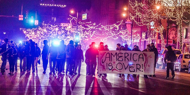 Police arrested protesters who marched with fireworks to Uptown in Minneapolis, Tuesday, Nov. 3, 2020. They were cornered at Painter Park by the police. (Richard Tsong-Taatarii/Star Tribune via AP)