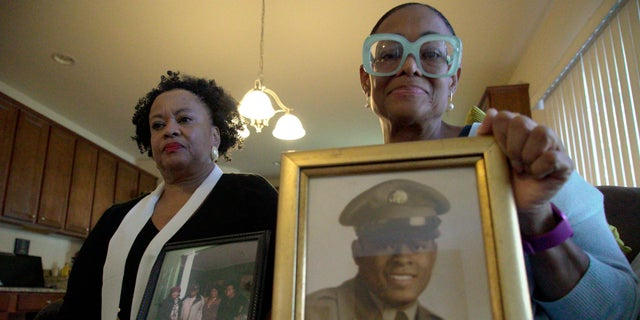 Sisters Barbara Leak-Watkins, right, and Alberta Lynn Fantroy pose with photos of their late father, Alex Leak Jr., an Army veteran who died in July after collapsing from dehydration at his assisted-living facility.