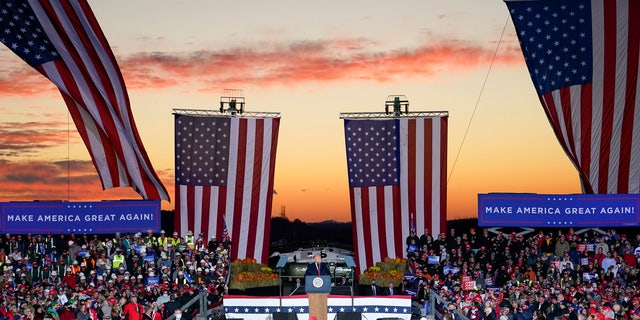 President Trump addresses the crowd as the sun sets during a campaign stop, Saturday, Oct. 31, 2020, at the Butler County Regional Airport in Butler, Pa.