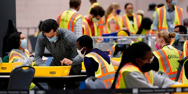Philadelphia election workers process mail-in and absentee ballots for the general election, at the Pennsylvania Convention Center, Tuesday, Nov. 3, 2020, in Philadelphia. (AP Photo/Matt Slocum)